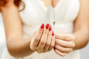 pretty fingers nails holding feather